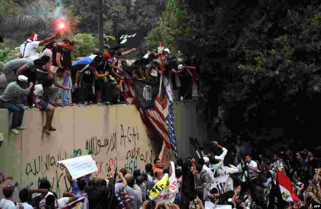 Des manifestants égyptiens escaladant le mur de l'ambassade amércaine en Egypte et agitant un drapeau islamiste