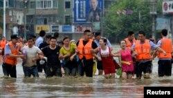 Polisi di kota Chengdu, provinsi Sichuan, China membantu para warga yang terjebak banjir (9/7).