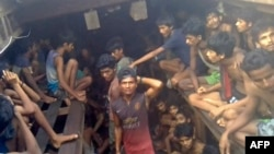 This video grab taken on December 4, 2020 from an AFPTV video shows a Burmese smuggler (C) along with Rohingya refugees in a boat in Chakmarkul on August 26, 2020. - As scores die on a ship packed with desperate Rohingya, Burmese smugglers mercilessly bea