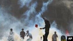 AbanyaTurkiya bariko baragira imyiyerekano, baratanye mu mitwe n'abapolisi mu kibanza citwa Taksim Square mu gisagara ca Istanbul