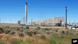 FILE--The Plutonium Uranium Extraction Plant (R) stands adjacent to a dirt-covered rail tunnel (L) containing radioactive waste, amidst desert plants on the Hanford Nuclear Reservation near Richland, Wash., June 13, 2017.