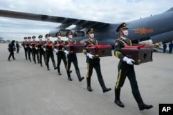 Tentara kehormatan China membawa peti yang berisi sisa-sisa jenazah tentara China, bergerak menuju pesawat kargo pada upacara serah terima di Bandara Internasional Incheon di Incheon, Korea Selatan, Kamis, 2 September 2021.