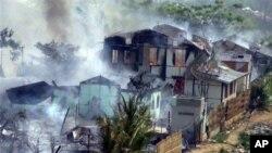 Asap nampak membumbung dari bangunan yang terbakar di Meikhtila, Burma tengah, di mana terjadi kerusuhan antara warga Buddha dan Muslim (foto, 21/3/2013).