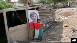 A Bedouin child stands in front of a picture of German Chancellor Angela Merkel ahead of her expected visit to Israel on Oct. 3, 2018, in the West Bank Bedouin community of Khan al-Ahmar, Oct. 2, 2018.