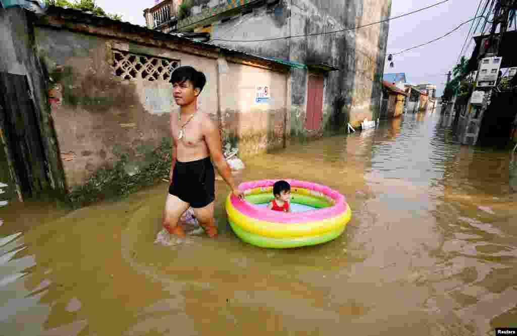 پدری که برای حمل دخترش در خیابانهای آب گرفته بر اثر بارش باران های سیل آسا در ویتنام از قابق بادی استفاده می کند.