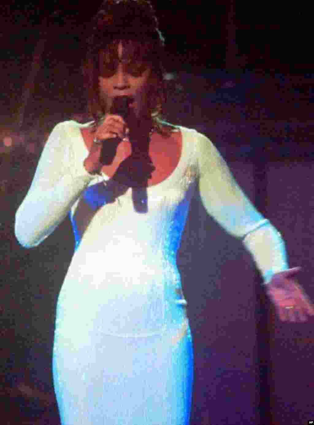 """Whitney Houston sings """"I Will Always Love You"""" during the opening of the 36th Annual Grammy Awards at New York's Radio City Music Hall on March 1, 1994. Houston later won Best Pop Female Vocal Performance for the song. (AP Photo/Ron Frehm)"""
