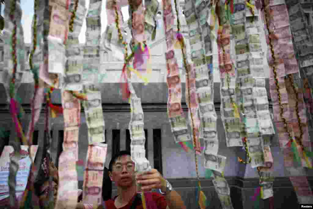 People decorate a temple with Thai banknotes ahead of the Chinese Lunar New Year celebrations in Bangkok's Chinatown, Thailand.