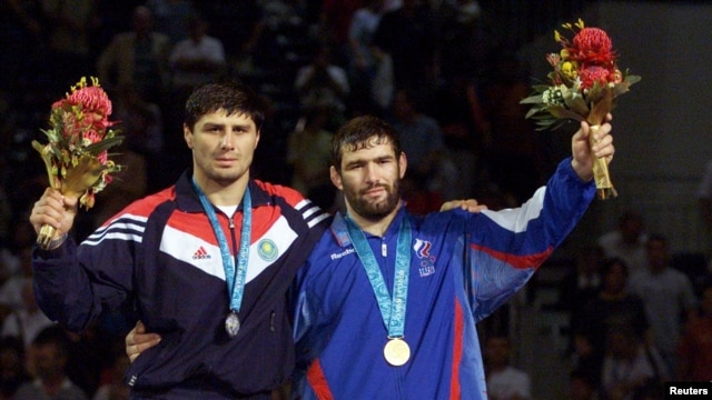 FILE - Gold medalist Sagid Mourtasaliyev (R) poses with silver medallist Islam Bairamukov at the Olympic Games in Sydney, September 30, 2000.