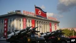 ທະຫານ ເກົາຫຼີເໜືອ ເດີນສວນສະໜາມຄັ້ງໃຫຍ່ຜ່ານ ຈະຕຸລັດ Kim Il Sung ພ້ອມກັບລູກສອນໄຟຂີປະນາວຸດ ແລະ ຈະຫຼວດຂອງພວກເຂົາ . 10 ຕຸລາ, 2015, ພຽງຢາງ, ເກົາຫຼີເໜືອ.