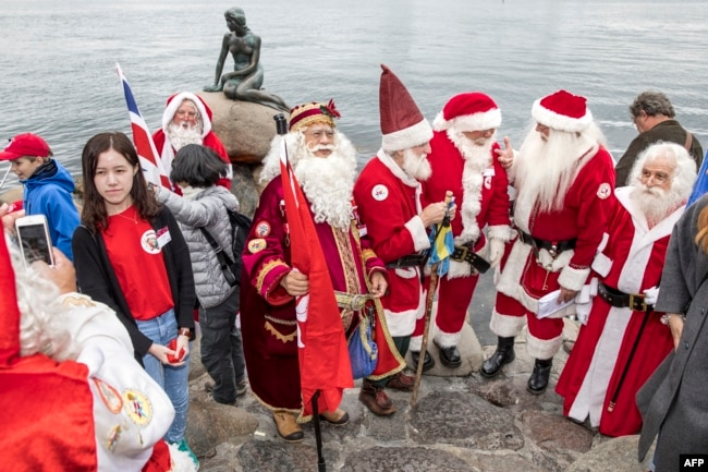 Participants of the Santa Claus World Congress visit the Little Mermaid statue in Copenhagen, Denmark.