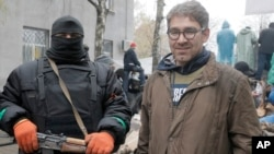 In this photo taken on April 13, 2014, American reporter Simon Ostrovsky, right, stands with a pro-Russian gunman near a police station in the eastern Ukrainian town of Slovyansk.