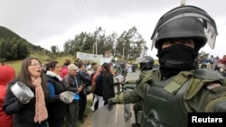 Demonstrators protest in front of riot policemen at the entrance of La Calera near Bogota, Aug. 28, 2013.