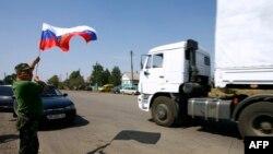 Một cư dân địa phương cầm cờ Nga trong khi những chiếc xe tải, một phần trong đoàn xe chở vật phẩm nhân đạo của Nga, đi qua biên giới Ukraine tại chốt kiểm tra hải quan ở Izvarino, 22/8/2014.