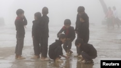 FILE - Children play during a class break on a foggy day, located on the China border on Sept. 21, 2015. Parents grew anxious after nearly 500 students from a middle school developed illnesses that are possibly linked contaminated soil and underground water adjacent to three former pesticide plants.
