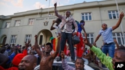 Zimbabweans celebrate outside the parliament building immediately after hearing the news that President Robert Mugabe had resigned, in downtown Harare, Zimbabwe, Nov. 21, 2017.
