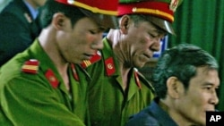 Vietnamese dissident priest Father Thadeus Nguyen Van Ly (R) is escorted by police as he faces a court in Vietnam's central Hue City in this March 30, 2007 file photo. He has since been freed for medical treatment.