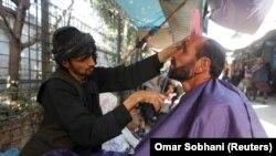 Seorang pria Afghanistan mencukur jenggotnya di sebuah pangkas rambut jalanan di Kabul, Afghanistan 11 Oktober 2017. (Foto: REUTERS/Omar Sobhani)