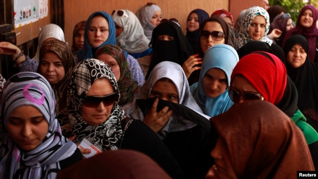 FILE - Women wait to vote at a polling station during national assembly elections in Tripoli, July 7, 2012.
