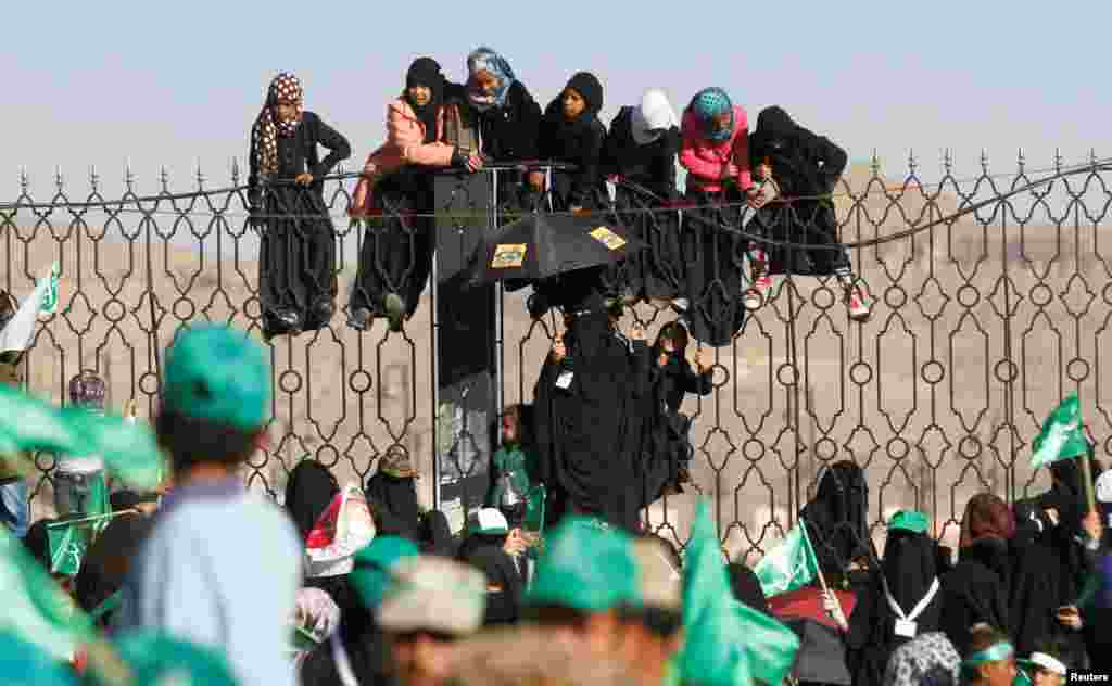 Houthi supporters hang off an iron fence during a rally marking the birth anniversary of Islam's Prophet Mohammad, in Sana'a, Yemen.