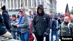 A man (center in black coat) identified by U.S. federal prosecutors as Shane Jason Woods of Auburn, Illinois. is seen in a frame grab from video shot during the Jan. 6, 2021 assault on the U.S. Capitol, moments before attacking members of the news media.