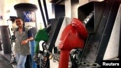 Un ciudadano observa un surtidor de gasolina encadenado debido a la falte de combustible en Caracas.