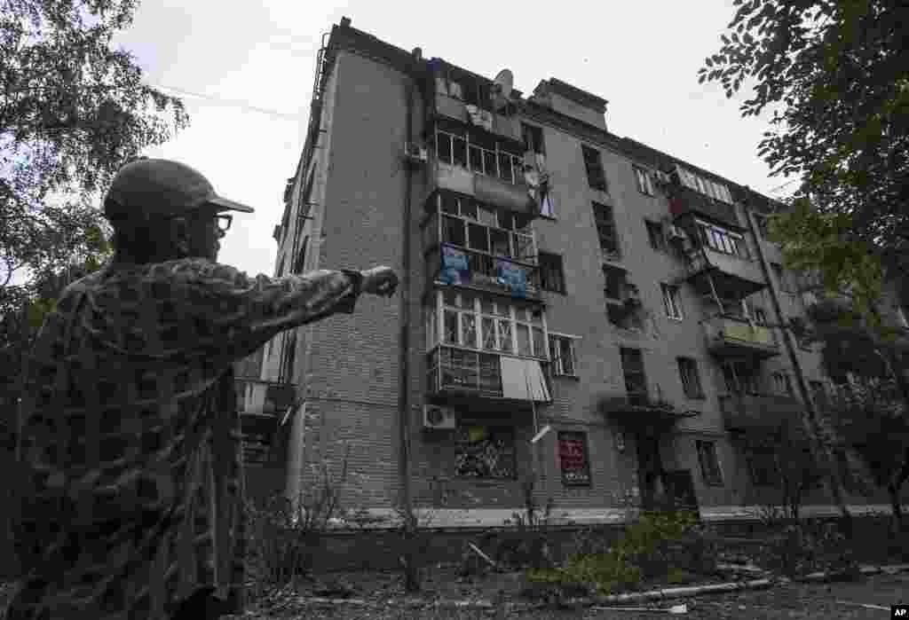 A resident shows an apartment building damaged by a mortar attack by Ukrainian government troops in Slovyansk, eastern Ukraine, June 9, 2014.