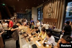 Customers are seen at a new Starbucks Reserve flagship store in Beijing's Qianmen area, China, June 30, 2018.