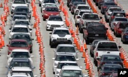 Lines of cars wait at a coronavirus testing site outside of Hard Rock Stadium, in Miami Gardens, Fla., June 26, 2020.