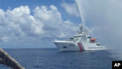 FILE - In this Sept. 23, 2015, file photo, Chinese Coast Guard members approach Filipino fishermen as they confront each other off Scarborough Shoal in the South China Sea, also called the West Philippine Sea. (AP Photo/Renato Etac, File)