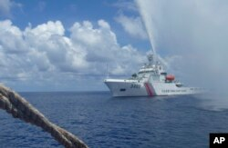 FILE - Chinese Coast Guard members approach Filipino fishermen as they confront each other off Scarborough Shoal in the South China Sea, Sept. 23, 2015.