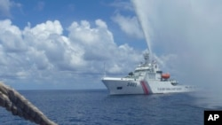 Chinese Coast Guard members approach Filipino fishermen as they confront each other off Scarborough Shoal in the South China Sea, on September 23, 2015.