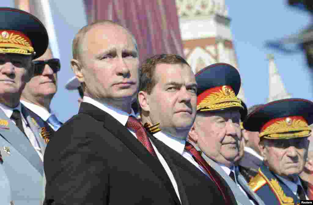 Russia's President Vladimir Putin (front L) and Prime Minister Dmitry Medvedev (C) watch the Victory Day parade in Moscow's Red Square.