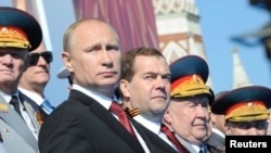 Presiden Rusia Vladimir Putin (depan, kiri) dan PM Dmitry Medvedev (tengah) mengamati parade Hari Kemenangan di Lapangan Merah, Moskow (9/5).