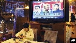 A woman eats a meal in a restaurant in Guangzhou, southern China Guangdong province while a television set reports on the successive North Korean leaders from left Kim Il Sung, Kim Jong Il and Kim Jong Un, December 20, 2011.