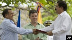 Honduras' President Porfirio Lobo, left, and Honduras' ousted President Manuel Zelaya, right, shake hands after signing an agreement as Colombia's President Juan Manuel Santos applauds in Cartagena, Colombia, May 22, 2011.