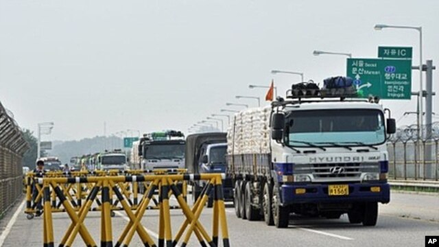 South Korean trucks carrying 300 tons of flour drive past a military checkpoint before crossing the inter-Korean border in Paju, north of Seoul, on July 26, 2011