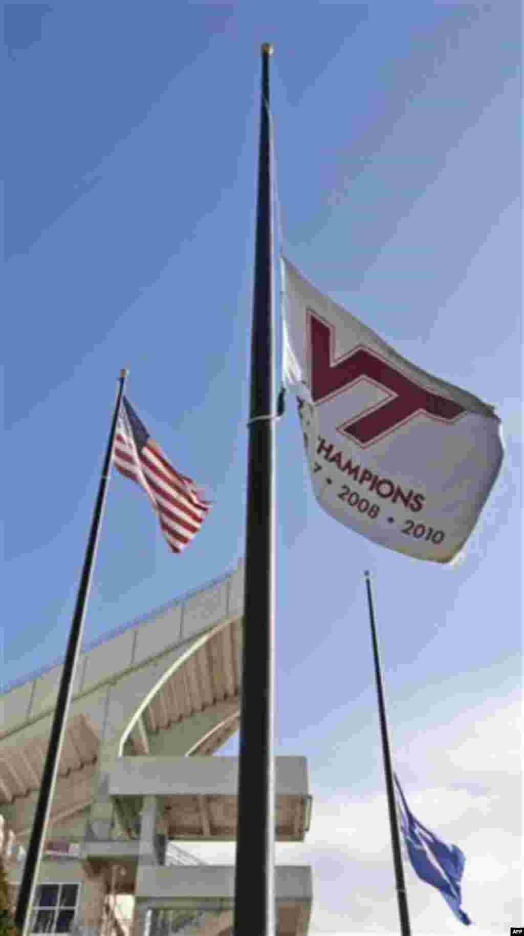 A Virginia Tech flag and the state of Virginia flag fly at half-staff in front of Lane Stadium on the campus of Virginia Tech in Blacksburg, Va., Friday, Dec. 9, 2011. A Virginia Tech police officer was shot and killed on campus Thursday. (AP Photo/Steve