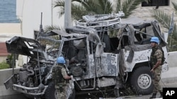 Two Italian UN peacekeepers stand guard next to a destroyed UN armored vehicle that attacked by a roadside bomb, in the southern port city of Sidon, Lebanon, May 27, 2011.