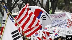 South Korean activists cheer as they wave flags of the United States and South Korea to celebrate the free trade agreement, or FTA, with the United States during a rally near the U.S. Embassy in Seoul, South Korea, March 14, 2012.