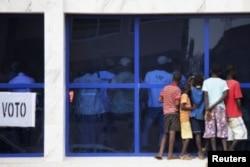 Des gamins regardent les responsables de la CNE durant le dépouillement à Bissau, le 18 mars 2012
