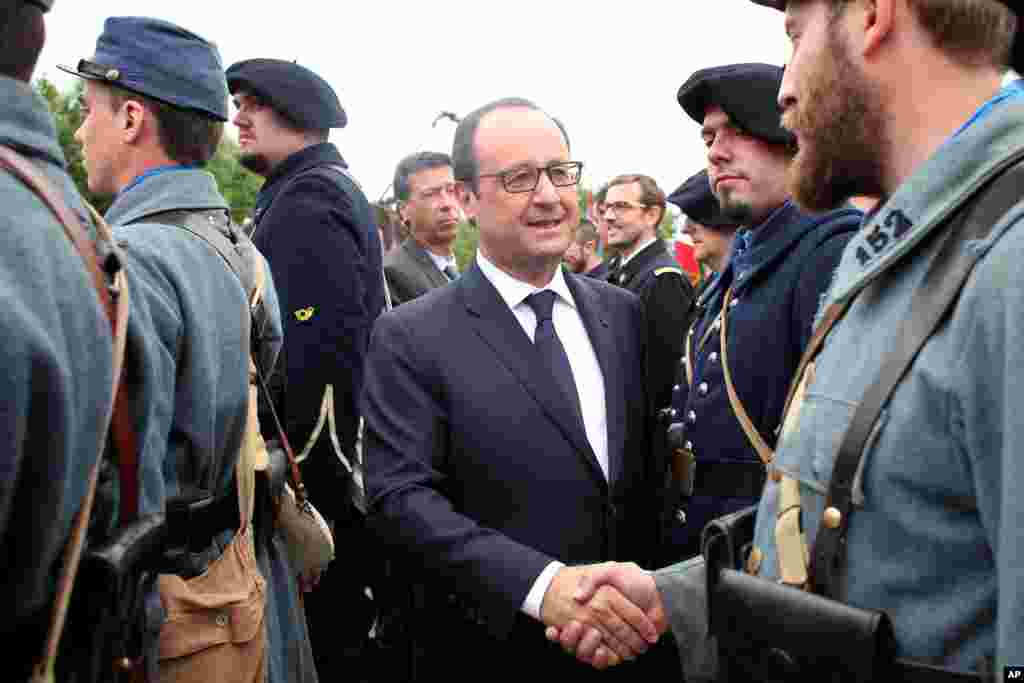 French President Francois Hollande shakes the hand of a man wearing a World War I uniform after a ceremony to mark the 100th anniversary of the outbreak of World War I, at the National Monument of Hartmannswillerkop, in Wattwiller, eastern France, Aug. 3, 2014.