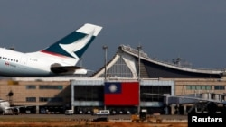 FILE - A Hong Kong Cathay Pacific Airways Airbus passenger plane takes off against the backdrop of a Taiwanese flag, at Taoyuan International Airport, Taiwan, Aug. 6, 2018.