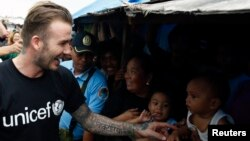 Former England soccer captain David Beckham greets victims of super Typhoon Haiyan at an evacuation center in Tacloban city in central Philippines February 13, 2014. Local officials said, Beckham is one of the biggest donors to super typhoon Haiyan devastated areas in central Philippines, February 13, 2014.