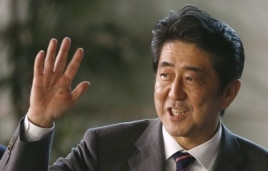 Japan's newly-named Prime Minsiter Shinzo Abe smiles as he waves at the media upon his arrival at the prime minister's official residence following his election at Parliament in Tokyo, December 26, 2012.