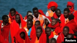 Migrants, part of a group intercepted aboard two dinghies off the coast in the Mediterranean Sea, stand on a rescue boat upon arrival at the port of Malaga, Spain, June 9, 2018.