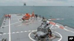 Sebuah helikopter tiba di landasan KRI Banda Aceh, dekat area di mana sebuah tim SAR menemukan ekor pesawat AirAsia QZ 8501 di Laut Jawa, Kamis, (8/1).