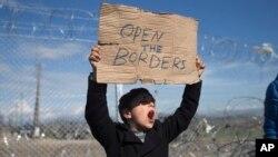 Un niño grita un eslogan mientras exhibe un cartel exigiendo que se abran las fronteras en Europa frente a una valla en la frontera de Grecia con Maceconia.