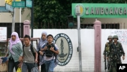 Warga desa setempat berupanya menyelamatkan diri dan mengungsi pasca bentrokan antara patroli angkatan laut Filipina dengan front pembebasan Islam Moro di kota Zamboanga, selatan Filipina (9/9).