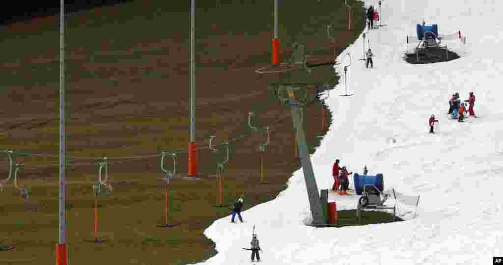 People enjoy the day at a ski hill prepared with artificial snow in Ruhpolding, southern Germany. Temperatures in southern Germany, are unusually high.