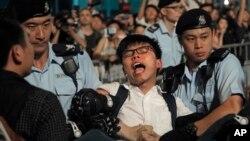 Aktivis pro-demokrasi Joshua Wong ditahan oleh petugas polisi setelah menaiki patung bunga raksasa yang diwariskan Beijing pada 1997 di Golden Bauhinia Square, Hong Kong, 28 Juni 2017.